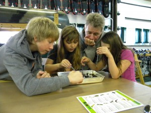 Wethead helping two students and a teacher find macro-invertebrates.