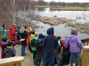 Wetheads assist students in using binoculars to see and identify various birds in the marsh.
